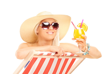 Trendy woman drinking a cocktail on a sun lounger isolated on white background photo