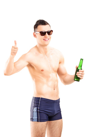 swimming shorts: Man in swim shorts holding a beer and giving thumb up isolated on white background