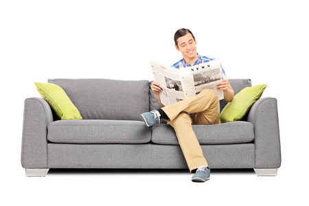 sit: Peaceful young man reading the news seated on sofa isolated on white background Stock Photo
