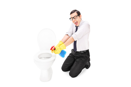 disinfecting: Man cleaning a toilet with disinfecting spray isolated on white background
