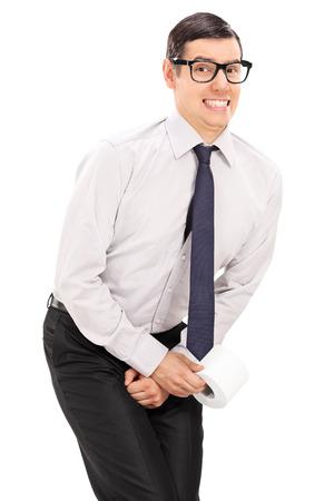 Tiro vertical de un hombre la necesidad de orinar y la celebración de un papel higiénico aisladas sobre fondo blanco