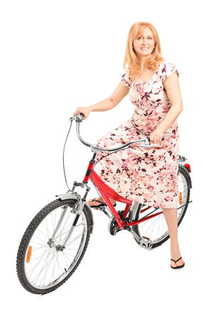 Mature lady posing seated on a bicycle isolated on white background photo