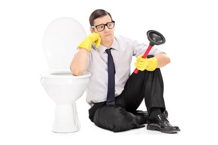 hombre sentado: Hombre triste que sostiene un émbolo y sentados en un inodoro aislado en fondo blanco Foto de archivo