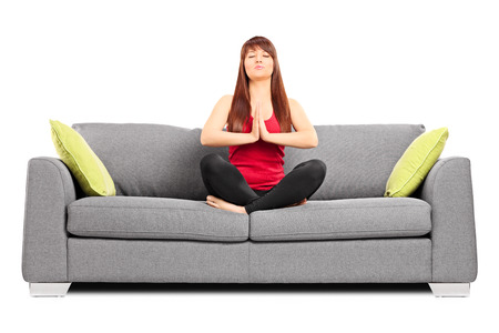 yoga pillows: Young girl meditating seated on a couch isolated on white background