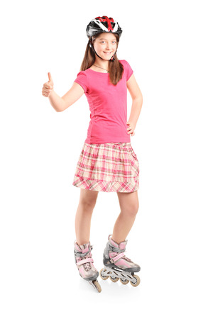 posing  agree: Full length portrait of a satisfied girl with a helmet on roller skates isolated on white background