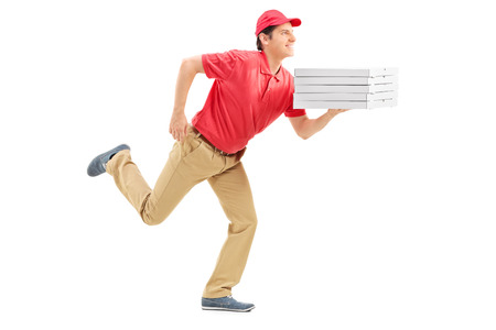 Profile shot of a pizza delivery guy running isolated on white background photo