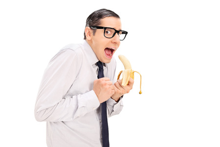 Scared man with glasses eating a banana isolated on white background photo