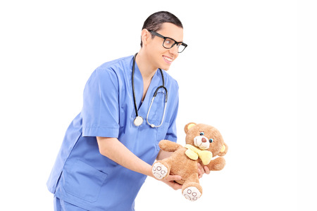 doctor holding gift: Young male doctor giving a teddy bear isolated on white background