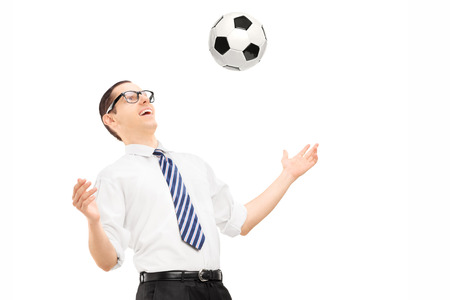 Young excited businessman playing with a soccer ball isolated on white background photo