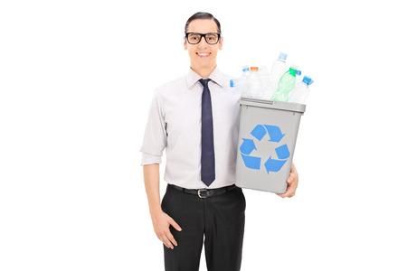 recycle bin: Hombre que sostiene una papelera de reciclaje llena de botellas de plástico aisladas sobre fondo blanco