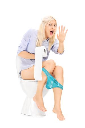 avergonzado: Una chica interrumpido sentado en un inodoro aislado en fondo blanco Foto de archivo