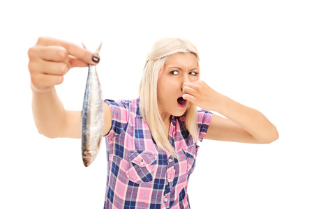 fish: Blond woman holding a stinky fish isolated on white background