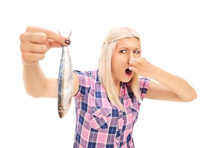 peces: Mujer rubia que sostiene un pescado apestoso aislado en fondo blanco Foto de archivo