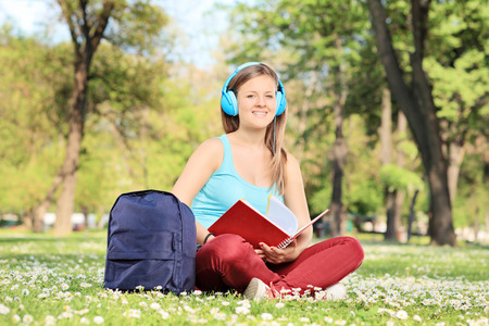 Female student studying on campus seated in a meadow full of flowers shot with tilt and shift lens photo