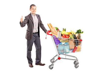 posing  agree: Satisfied man with a cart full of groceries isolated on white background