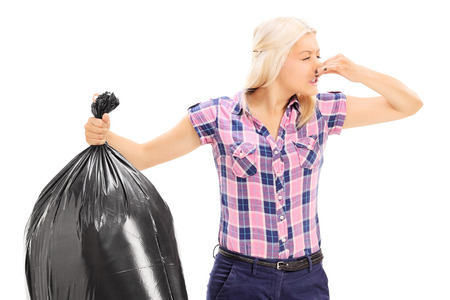 Woman holding a smelly garbage bag isolated on white background Stock Photo
