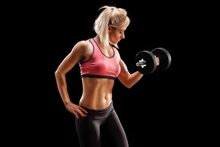 expresion corporal: Culturista femenina atractiva levantar una barra en el fondo negro