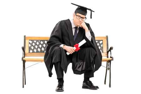 Angry college graduate holding a diploma isolated on white background