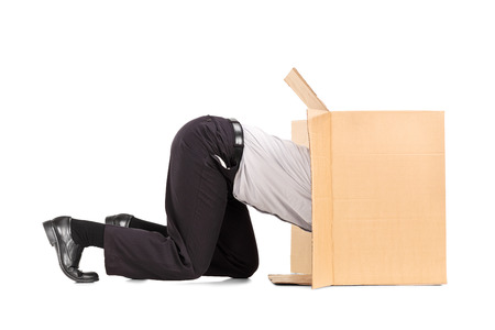 Businessman squeezing himself into a box isolated on white background photo