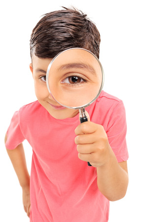 investigating: Little boy looking through a magnifying glass isolated on white background