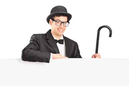Male performer holding a cane behind a panel isolated on white background photo