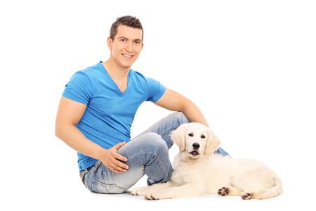 chilling out: Hombre pasando el rato con su cachorro sentado en el suelo aislado en el fondo blanco