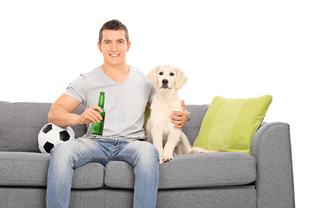 Man sitting at couch with his puppy and football isolated on white background photo
