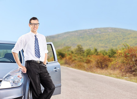 open car door: Happy young man standing by a car on an open road