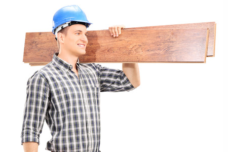 Handsome carpenter carrying a couple of planks isolated on white background photo