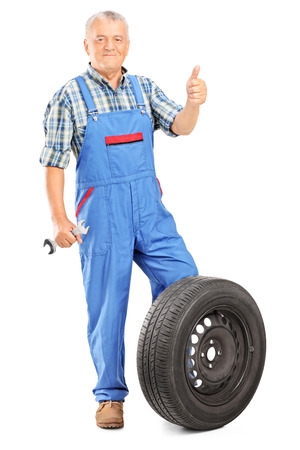 posing  agree: Mature mechanic giving a thumb up and holding a wrench isolated on white background