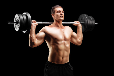 weightlifter: Weightlifting athlete lifting a barbell on black background Stock Photo