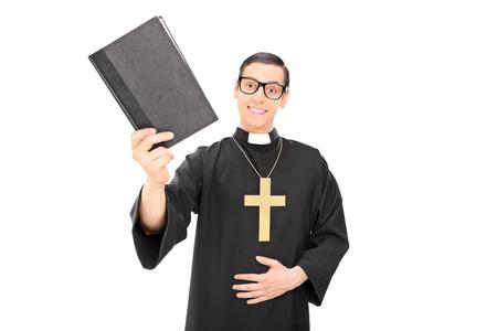 sacerdote: Sacerdote joven feliz que sostiene una biblia santa aislado en el fondo blanco
