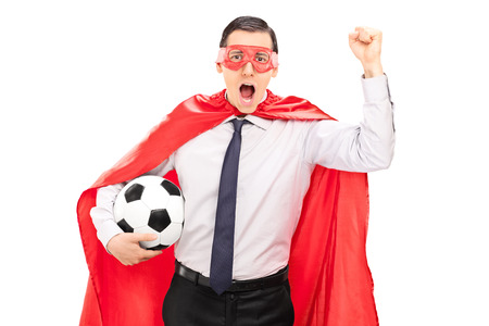 fanatic studio: Superhero cheering and holding a football isolated on white background