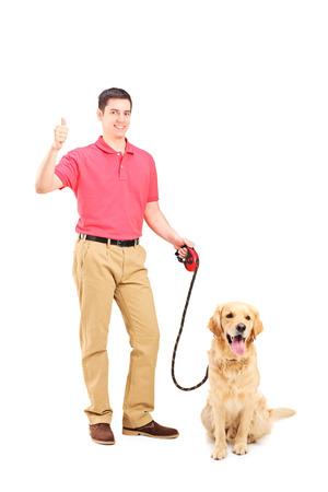 Jonge man met een hond het geven duim omhoog op een witte achtergrond Stockfoto