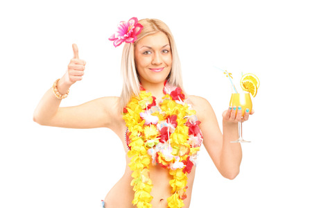 Woman in hawaiian costume drinking cocktail and giving thumb up isolated on white background  photo
