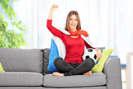 dutch girl: Female football fan with Dutch flag cheering seated on sofa at home
