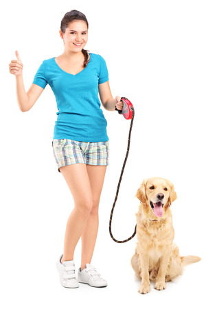 Full length portrait of a girl with a dog giving a thumb up isolated on white background photo