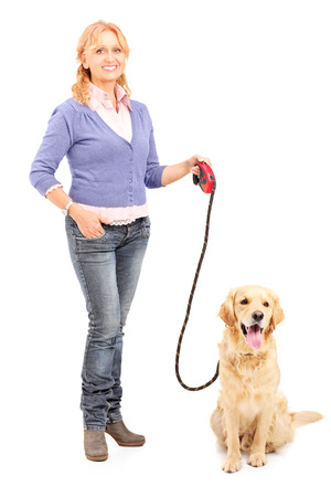 Full length portrait of a mature lady holding a dog on a leash isolated on white background photo