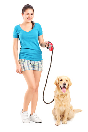 Full length portrait of a young girl walking a dog isolated on white background photo