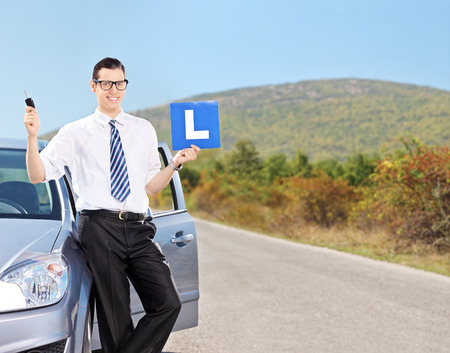 open car door: Male driver holding l sign and a car key on an open road shot with tilt and shift lens Stock Photo