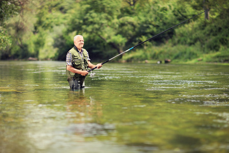 downstream: Mature fisherman fishing in a river with a fishing rod