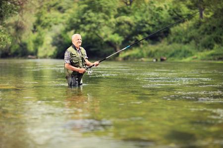 Rijpe visser die in een rivier met een hengel