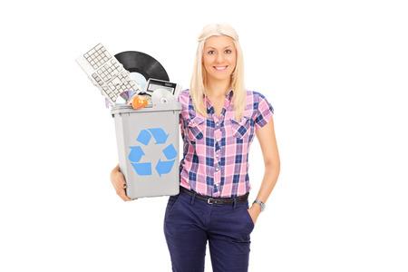 papelera de reciclaje: Muchacha que sostiene la papelera de reciclaje llena de accesorios antiguos aislados sobre fondo blanco