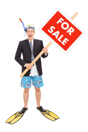 Full length portrait of a businessman with snorkel holding for sale sign isolated on white background photo