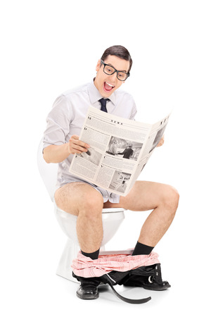 Joyful man reading the news seated on a toilet isolated on white background photo