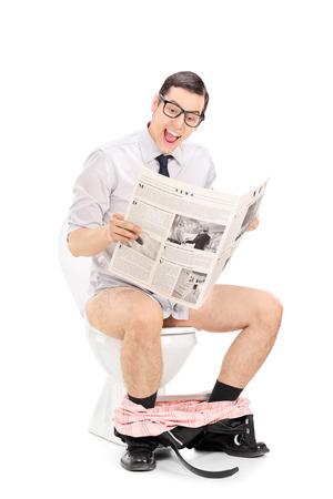 Joyful uomo che legge la notizia seduto su un gabinetto isolato su sfondo bianco Archivio Fotografico - 31488761