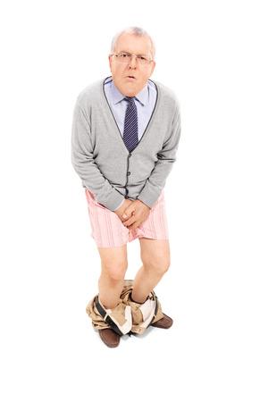 pantalones abajo: Mayor con los pantalones abajo sosteniendo su entrepierna aislados sobre fondo blanco