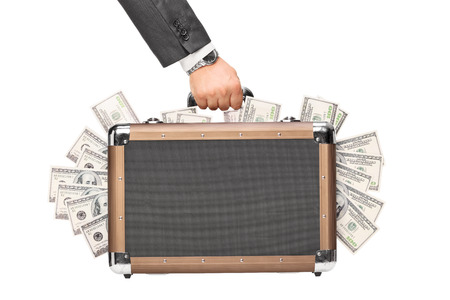 Hand holding a briefcase full of money isolated on white background photo