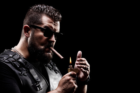Badass biker lighting up a cigarette on black background