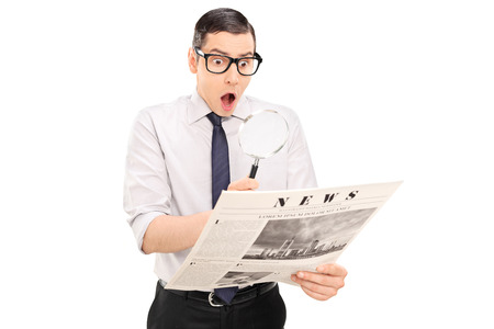 shock: Shocked man reading the news through a magnifier isolated on white background Stock Photo